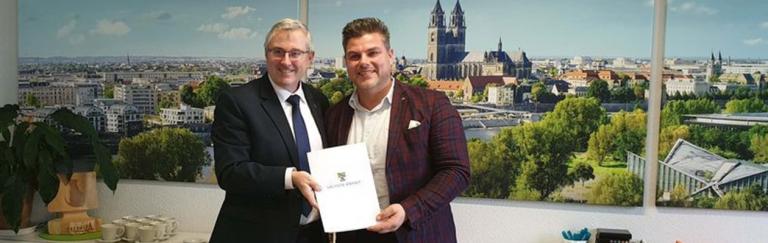 Staatssekretär Dr. Jürgen Ude (l.) überreicht die Fördermittelbewilligung für den Neubau der HASOMED-Firmenzentrale an Geschäftsführer Matthias Weber. © HASOMED